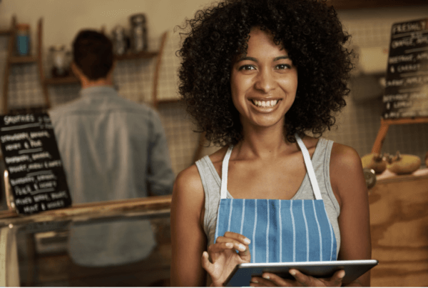 Business owner holding a tablet and enjoying a Successful Omnichannel Customer Experience Strategy