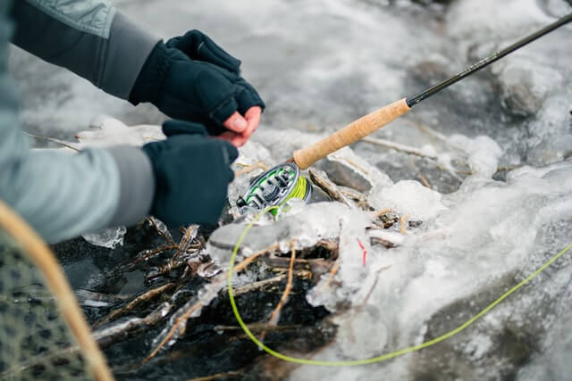 photo of a person adjusting their fly fishing equipment